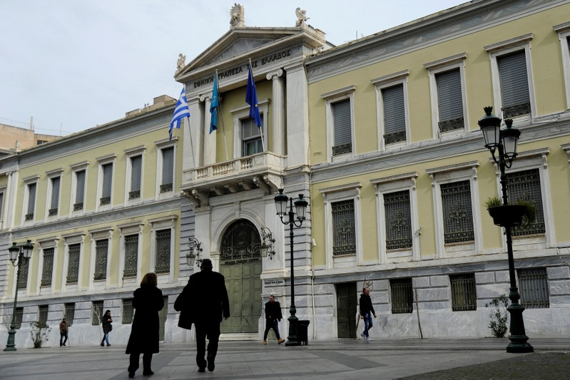 People make their way past the National Bank of Greece headquarters in central Athens