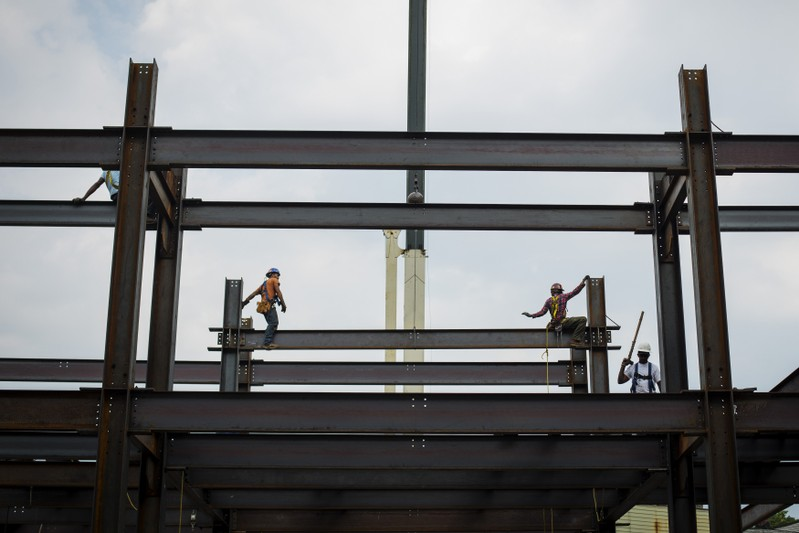 Iron workers install steel beams during a hot summer day in New York