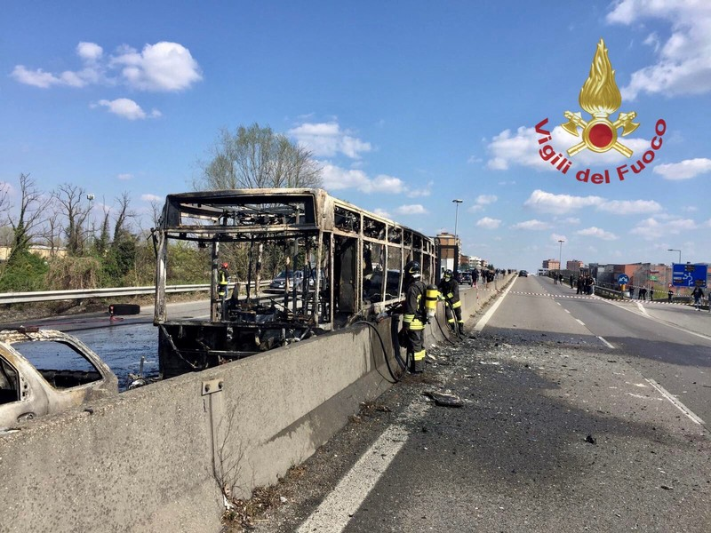The wrecakge of a burnt out bus is seen on a road in Milan