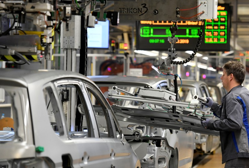 FILE PHOTO: An employee moves car components in a production line at the Volkswagen plant in Wolfsburg