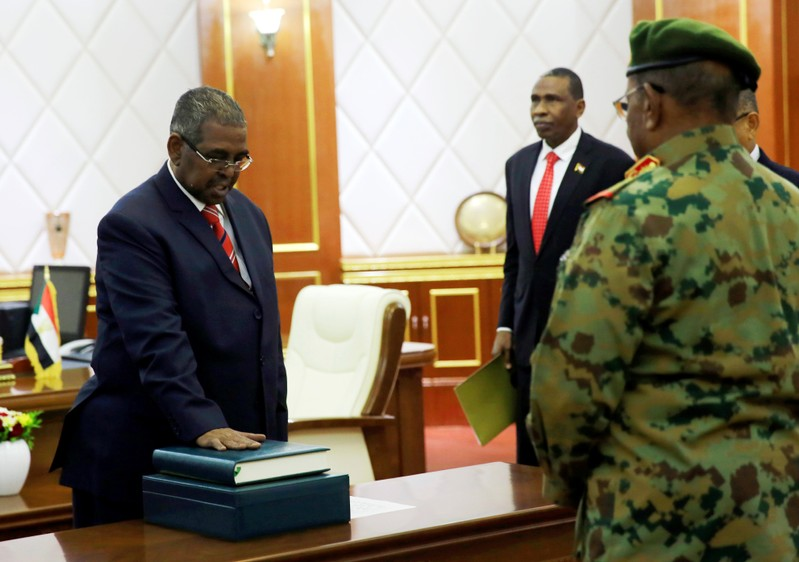 Mohamed Tahir Ayala is sworn in as prime minister in front of Sudan's President Omar al-Bashir during a swearing in ceremony in Khartoum