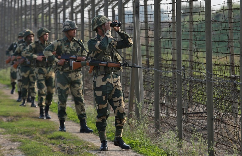 FILE PHOTO: India's Border Security Force soldiers patrol along the fenced border with Pakistan in Ranbir Singh Pura sector