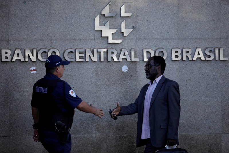 FILE PHOTO: People walk outside the central bank headquarters building in Brasilia