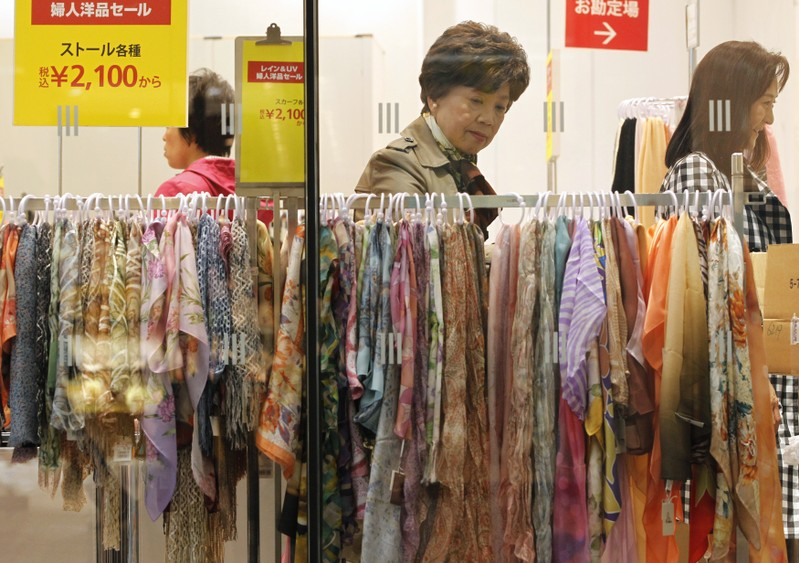 FILE PHOTO: A woman looks at scarves on sale at a department store in Tokyo