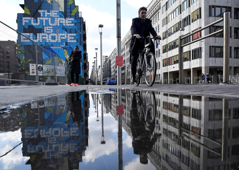 People are reflected in a puddle as they pass by a mural near the EU headquarters in Brussels