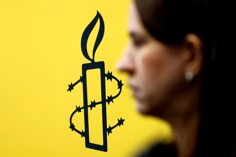 FILE PHOTO: The logo of Amnesty International is seen next to director of Mujeres En Linea Luisa Kislinger, during a news conference in Caracas