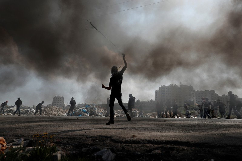 Palestinian protesters hurl stones at Israeli troops during clashes near the Jewish settlement of Beit El, in the Israeli-occupied West Bank