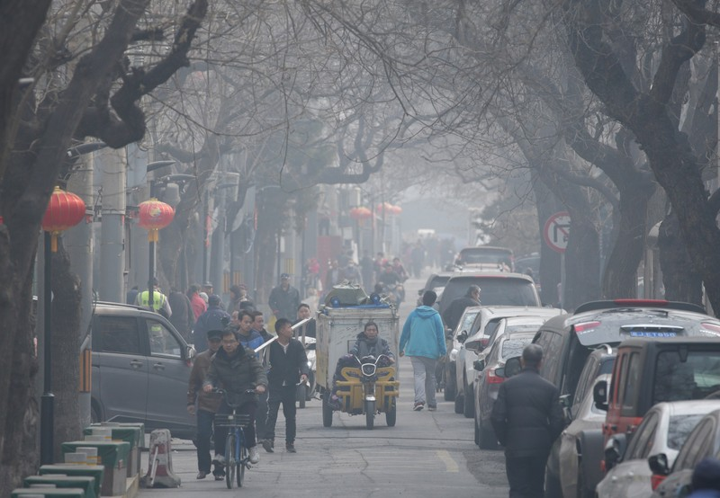 People are seen in a traditional alleyway on a polluted day in central Beijing
