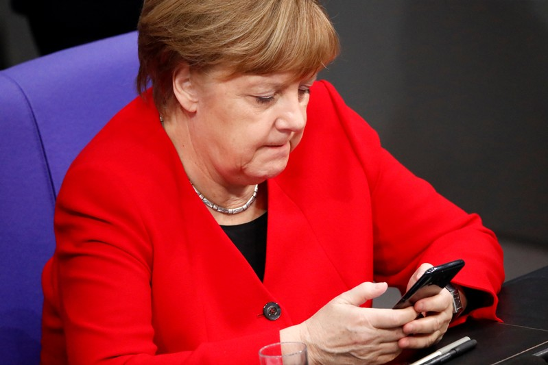German Chancellor Merkel checks phone at Bundestag ahead of EU summit on Brexit delay in Berlin