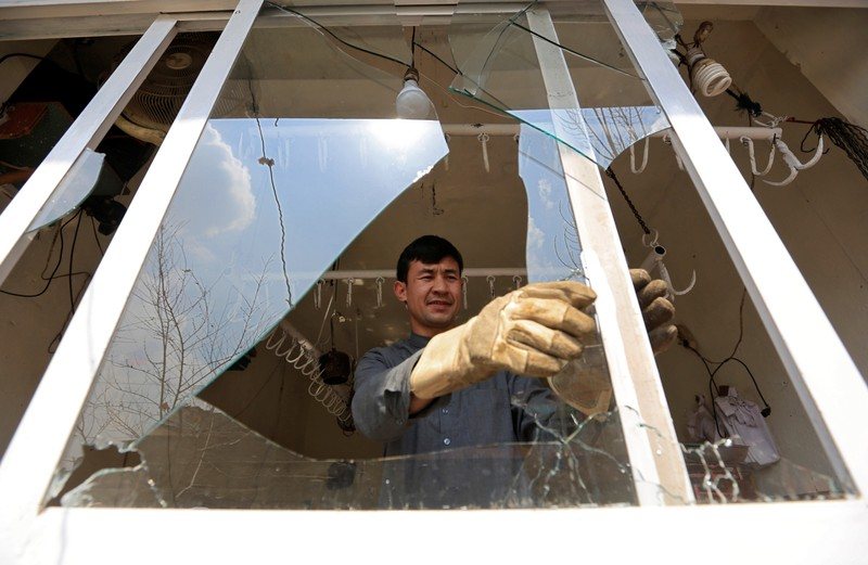 A man removes broken glass from a window after multiple explosions in Kabul