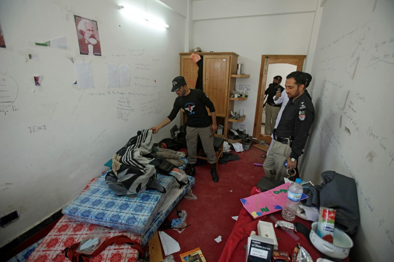 FILE PHOTO: Police search the dorm room of Mashal Khan, accused of blasphemy, who was killed by a mob at Abdul Wali Khan University in Mardan