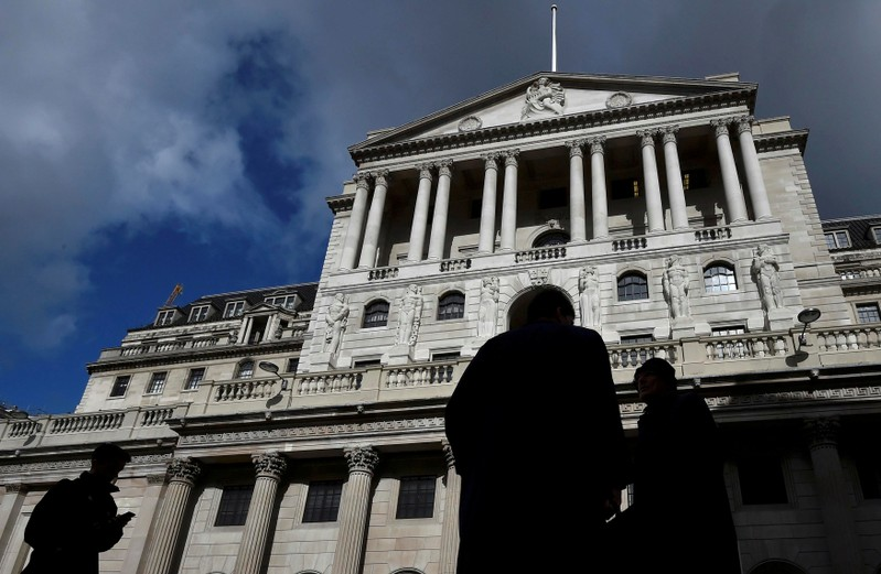 FILE PHOTO: File photo of city workers walking past the Bank of England in the City of London