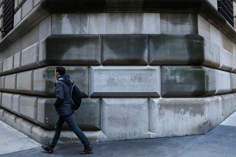 A man passes by the corner stone on the Federal Reserve Bank of New York in the financial district in New York