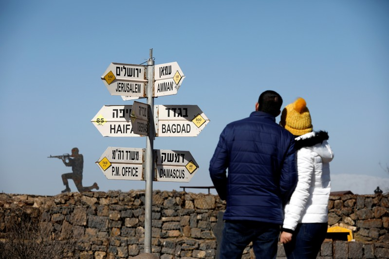 FILE PHOTO: A couple look towards signs pointing out distances to different cities,at an observation post in the Israeli-occupied Golan Heights