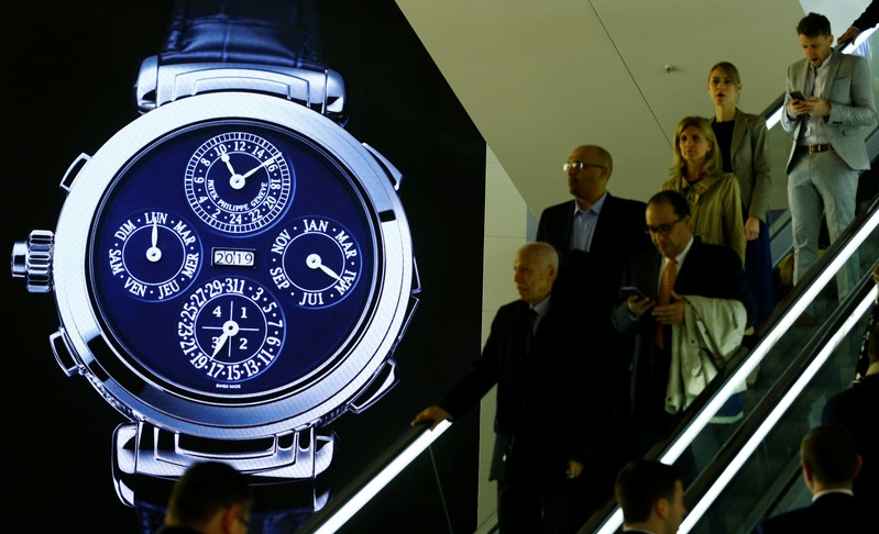 Visitors are seen in front of a display of Swiss watch manufacturer Patek Philippe at the Baselworld watch and jewellery fair in Basel