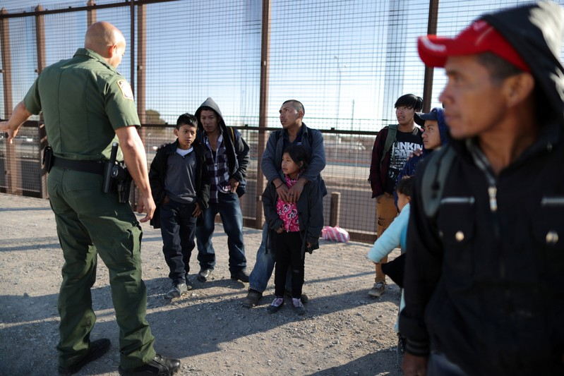 FILE PHOTO: A group of Central American migrants is questioned about their children's health after surrendering to U.S. Border Patrol Agents south of the U.S.-Mexico border fence in El Paso