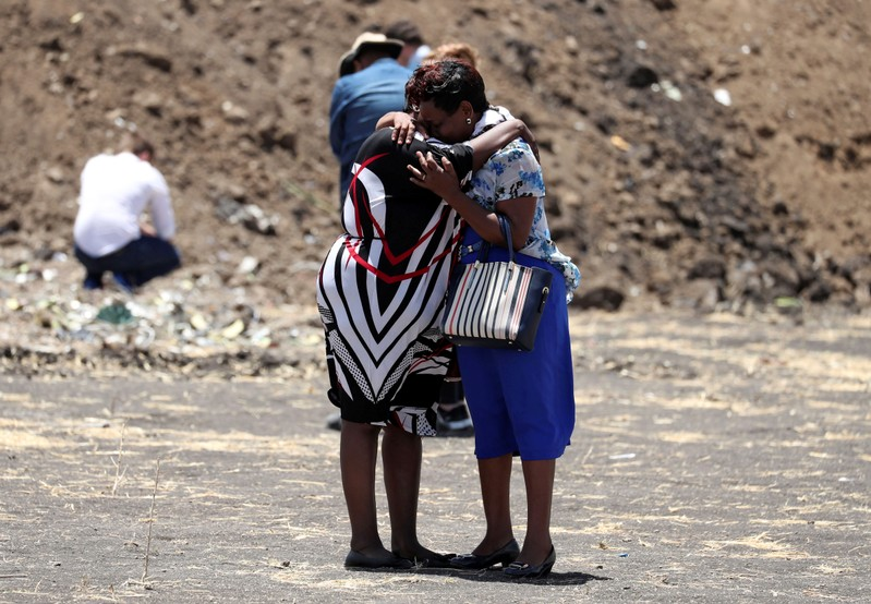 United Nations workers mourn their colleagues during a commemoration ceremony for the victims at the scene of the Ethiopian Airlines Flight ET 302 plane crash, near the town Bishoftu