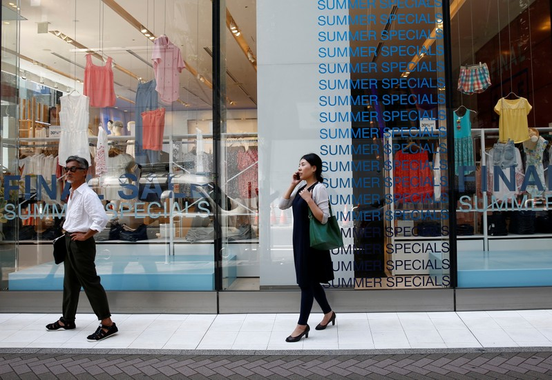 FILE PHOTO: Pedestrians stand in front of sale signs on a shopfront at a shopping district in Tokyo