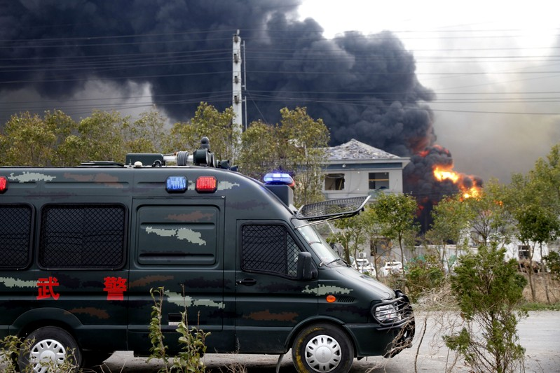 Vehicle of paramilitary police is seen near smoke following an explosion at a chemical industrial park in Xiangshui