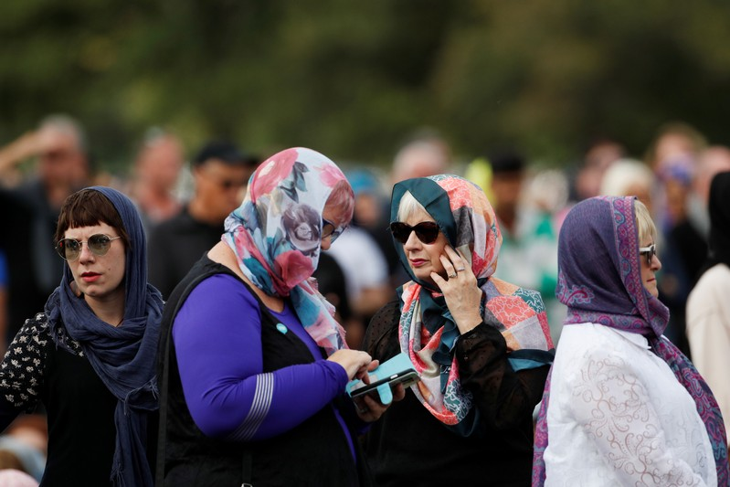 Women wearing headscarves as tribute to the victims of the mosque attacks are seen before Friday prayers at Hagley Park outside Al-Noor mosque in Christchurch