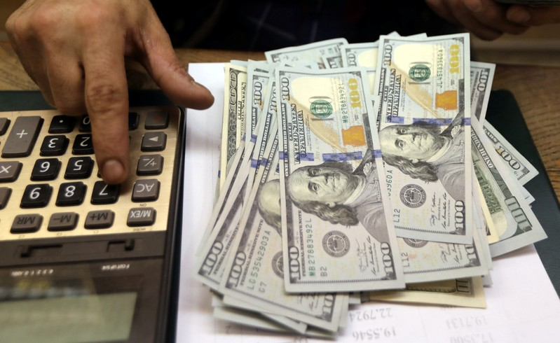 An employee counts U.S. dollar bills at a money exchange office in central Cairo