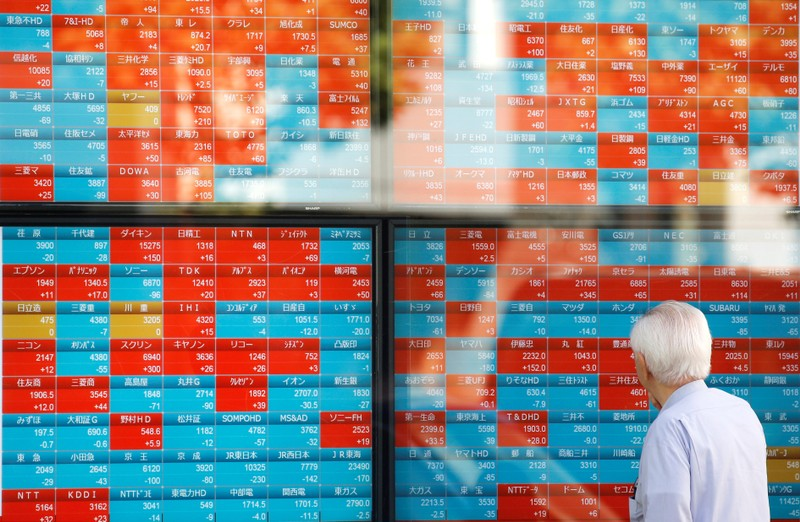 FILE PHOTO: A man looks at an electronic stock quotation board outside a brokerage in Tokyo