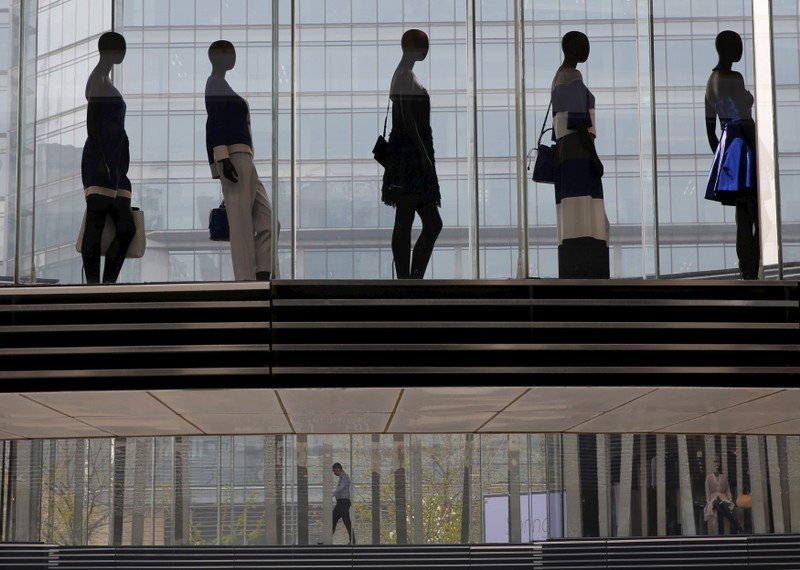 A man is seen walking under mannequins at a shopping mall in Beijing