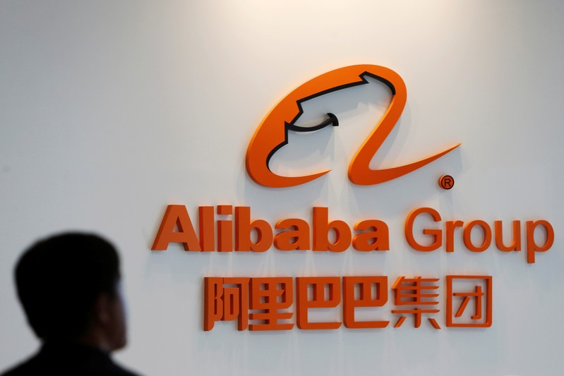 FILE PHOTO: A man stands near the logo of Alibaba Group at the company's newly-launched office in Kuala Lumpur