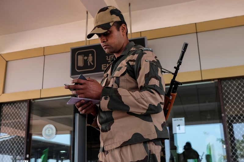 BSF soldier checks the passport of an Indian passenger from the 'friendship bus' between Indian and Pakistan at the Wagah-Attari border crossing