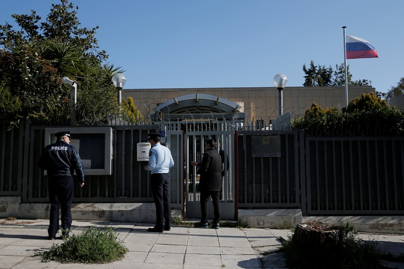 Police officers stand outside the Russian consulate after an explosion, in Athens