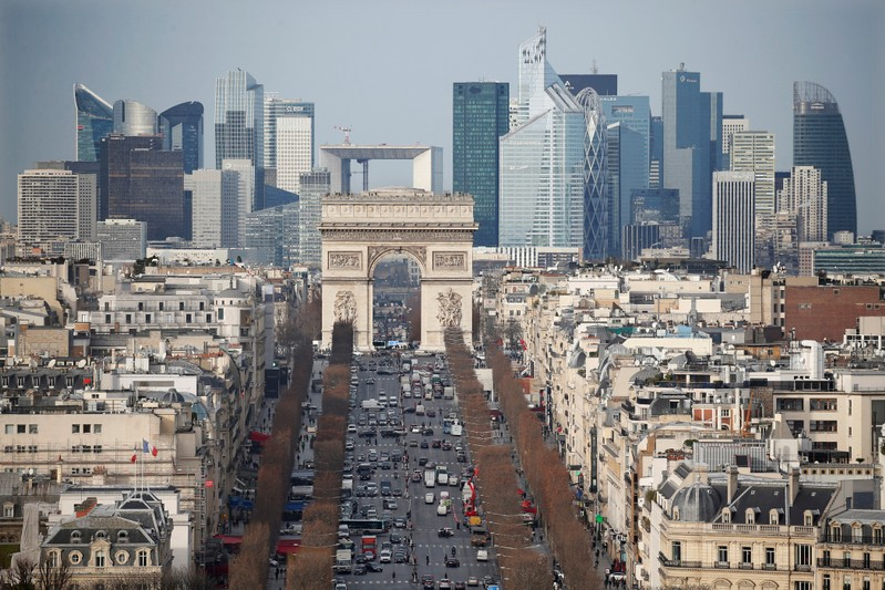 General view of the skyline of La Defense business district with its Arche behind Paris' landmark, the Arc de Triomphe and the Champs Elysees avenue in Paris