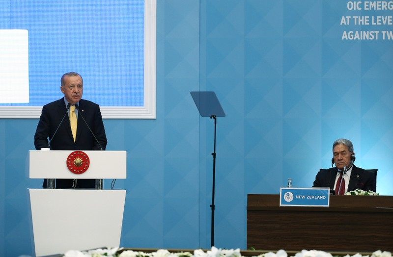 Turkish President Erdogan makes a speech as New Zealand's Foreign Minister Winston listens in Istanbul