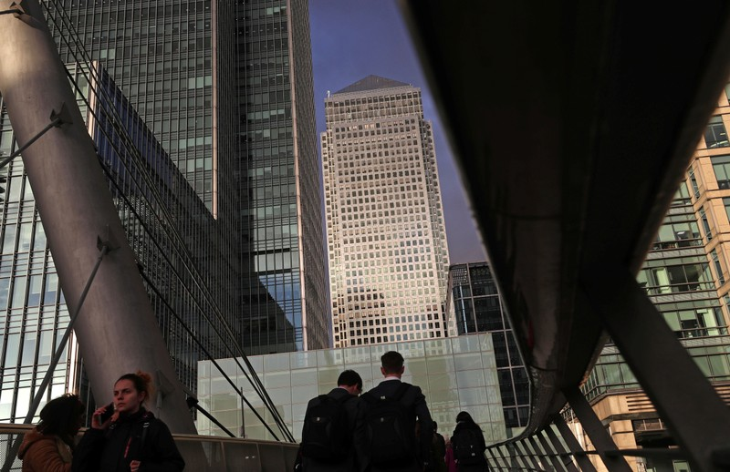 People walk through the Canary Wharf financial district of London
