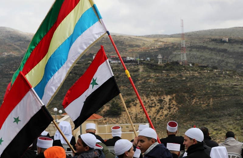 Members of the Druze community holds Syrian and Druze flags as they sit facing Syria, during a rally marking the anniversary of Israel's annexation of the Golan Heights in the Druze village of Majdal Shams, in the Israeli-occupied Golan Heights