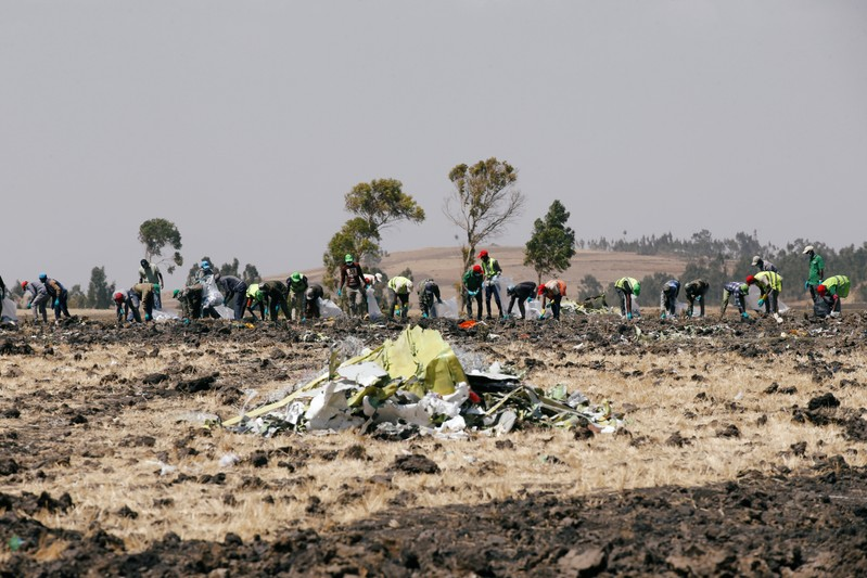 Ethiopians search for remains at the Ethiopian Airlines Flight ET 302 plane crash before a commemoration ceremony at the scene of the of the crash, near the town of Bishoftu, southeast of Addis Ababa