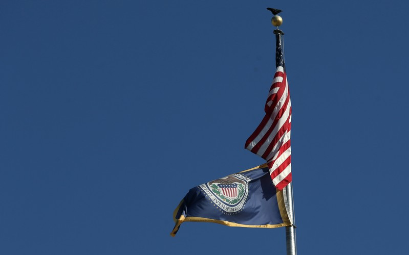 Flags are pictured at the top of Federal Reserve Board building on Constitution Avenue in Washington