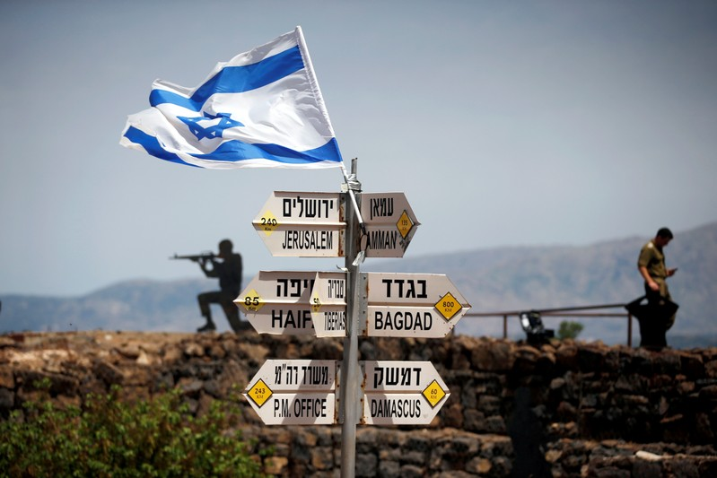 FILE PHOTO: An Israeli soldier stands next to signs pointing out distances to different cities, on Mount Bental, an observation post in the Israeli-occupied Golan Heights that overlooks the Syrian side of the Quneitra crossing