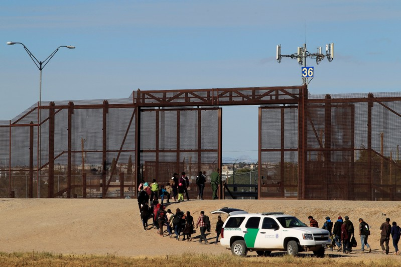 FILE PHOTO: Migrants from Central America are seen escorted by U.S. Customs and Border Protection officials after crossing the border from Mexico to surrender to the officials in El Paso, Texas, U.S., in this pictured taken from Ciudad Juarez