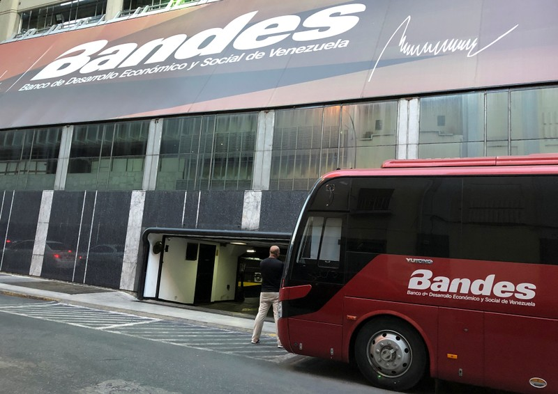 A man stands outside the Bandes bank headquarters in Caracas