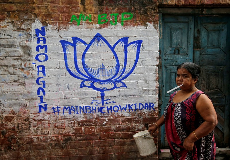 A woman walks past a wall painted with the election symbol of India's ruling Bharatiya Janata Party in an alley at a residential area in Kolkata