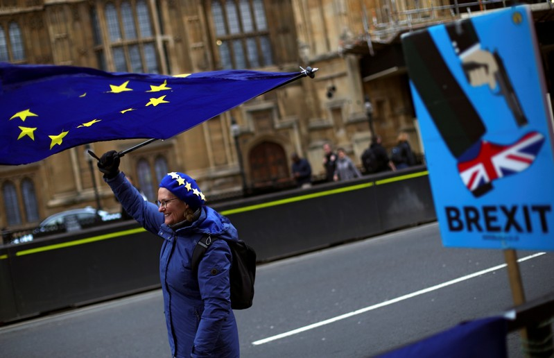 An anti-Brexit protester waves an EU flag outside the Houses of Parliament in London