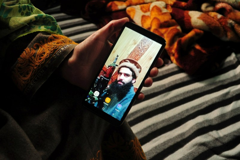 Sister of Owais Malik, a suspected militant, displays her phone with the picture of Malik, at her home in south Kashmir's Kulgam district