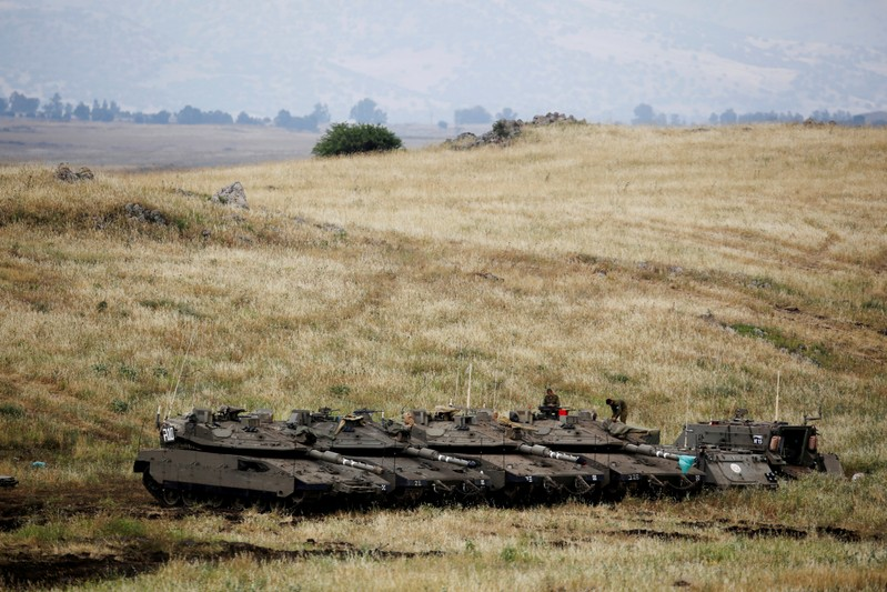 FILE PHOTO: Israeli soldiers stand on tanks near the Israeli side of the border with Syria in the Israeli-occupied Golan Heights