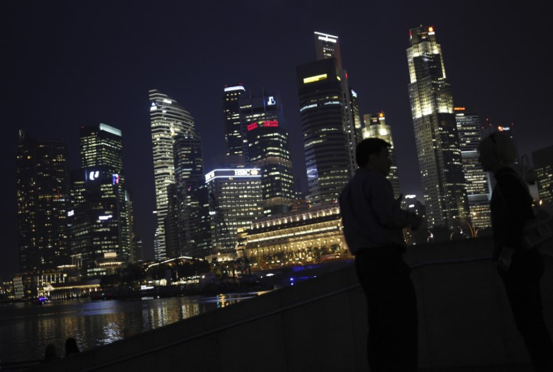 People chat as the skyline of Singapore's financial district is seen in the background