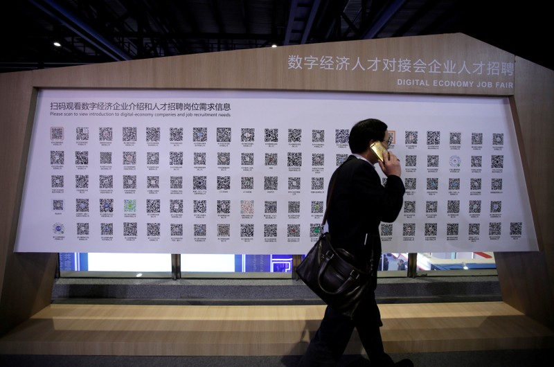 FILE PHOTO: A man walks past a poster showing the QR codes for job-seeking information during an internet expo at the fifth WIC in Wuzhen