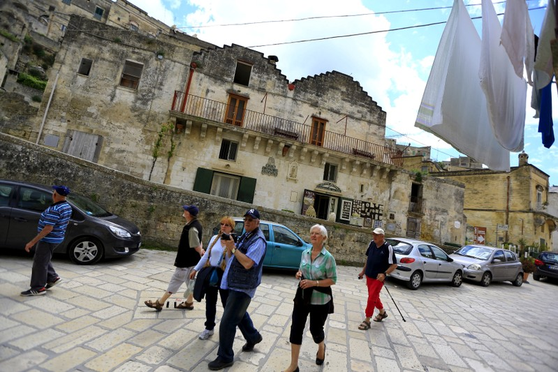 FILE PHOTO: Tourists walk on a street in Matera, southern Italy