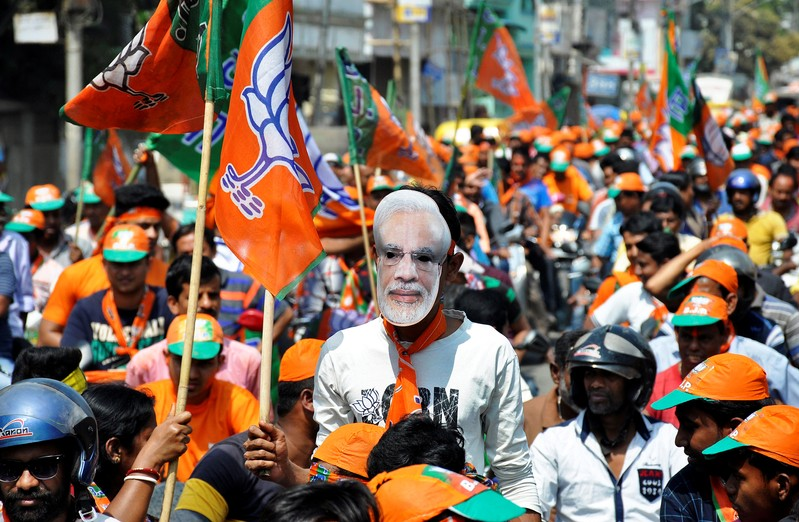 A Bharatiya Janata Party (BJP) supporter wears a mask of Prime Minister Narendra Modi, after BJP won complete majority in Tripura Assembly elections, during a victory celebration rally in Agartala