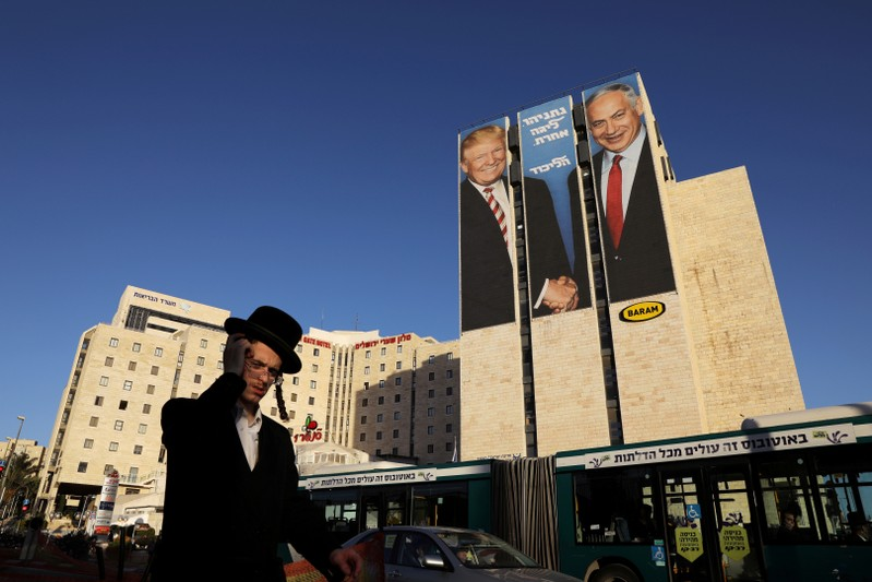 FILE PHOTO: A man walks past a Likud election campaign billboard depicting U.S. President Trump shaking hands with Israeli PM Netanyahu, in Jerusalem