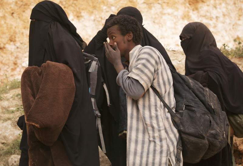 FILE PHOTO: Islamic state militant and women walk as they surrendered in the village of Baghouz, Deir Al Zor province