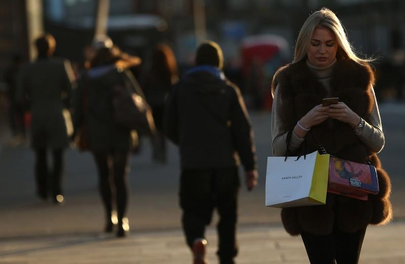 A woman checks her phone as she walks across London Bridge in London